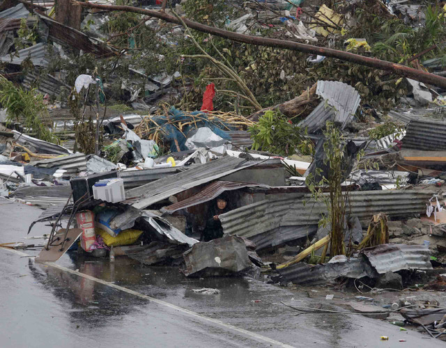 A woman looks out from the remains of her damaged house in Tacloban city, Leyte province, central Philippines on Sunday, Nov. 10, 2013. The city remains littered with debris from damaged homes as  ...
