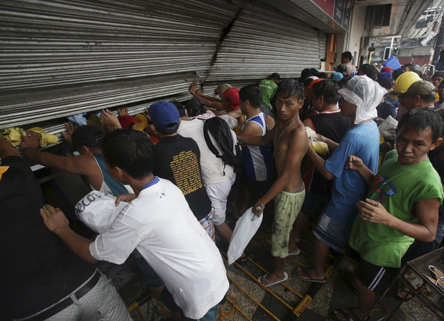 Residents push a shutter to open a small grocery to get food in Tacloban city, Leyte province central Philippines on Sunday, Nov. 10, 2013. The city remains littered with debris from damaged homes ...