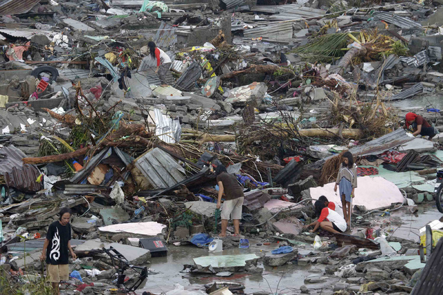 Residents try to salvage belongings in Tacloban city, Leyte province, central Philippines on Sunday, Nov. 10, 2013. The city remains littered with debris from damaged homes as many complain of sho ...