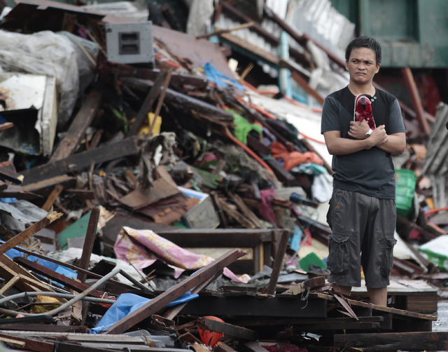 A resident looks at houses damaged by typhoon Haiyan, in Tacloban city, Leyte province central Philippines on Sunday, Nov. 10, 2013. Haiyan, one of the most powerful typhoons ever recorded slammed ...