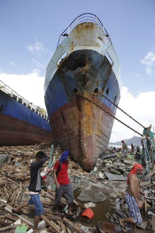 Survivors walk by a large ship after it was washed ashore by strong waves caused by powerful Typhoon Haiyan in Tacloban city, Leyte province, central Philippines on Sunday, Nov. 10, 2013. The city ...