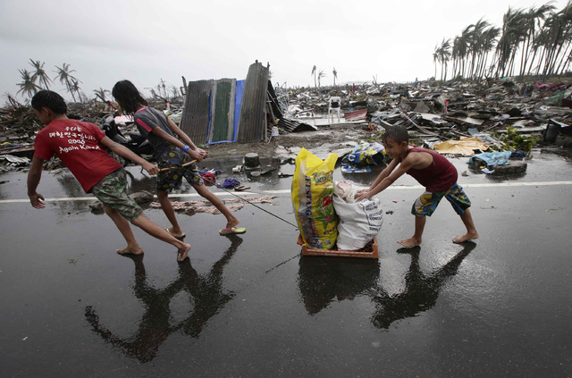 Residents carry relief goods past damaged homes in Tacloban city, Leyte province, central Philippines on Sunday, Nov. 10, 2013. The city remains littered with debris from damaged homes as many com ...