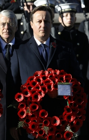 Britain's Prime Minister David Cameron holds a wreath during the service of remembrance at the Cenotaph in Whitehall, London, Sunday, Nov. 10, 2013. The annual remembrance service is to remember t ...