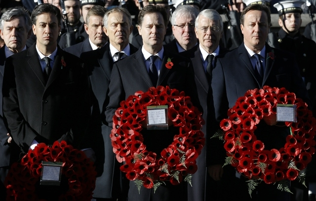 Britain's Prime Minister David Cameron, right, Deputy Prime Minister Nick Clegg, front centre, and Opposition Leader Ed Miliband, front left, hold wreaths during the service of remembrance at the  ...