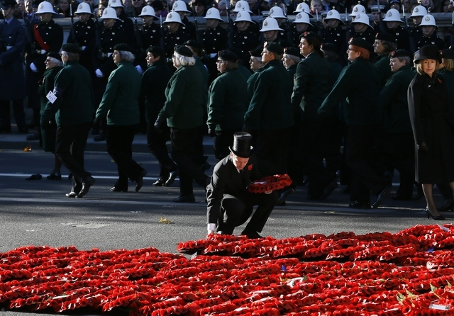 A steward places a wreath during the service of remembrance at the Cenotaph in Whitehall, London, Sunday, Nov. 10, 2013. The annual remembrance service is to remember those who have lost their liv ...