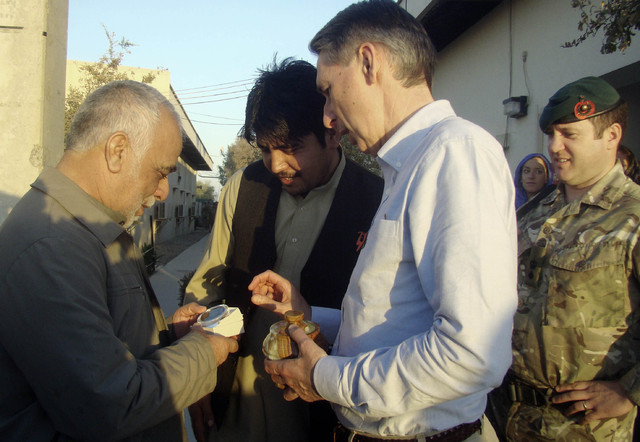 British Secretary of State for Defense Philip Hammond, center, receives a present from Helmand governor Mohammad Naeem, left, at the headquarters of the Provincial Reconstruction Team (PRT) in Las ...