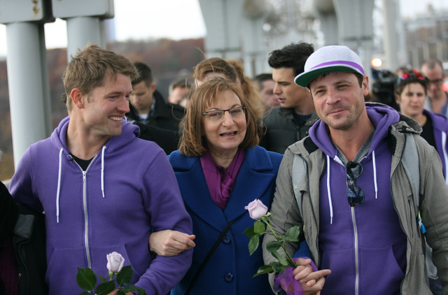 Ronnie Kroell, left, Tyler Clementi's mother Jane Clementi and Elliot London link arms as they walk across the George Washington Bridge to New York City on Sunday, Nov. 10, 2013, to help raise awa ...