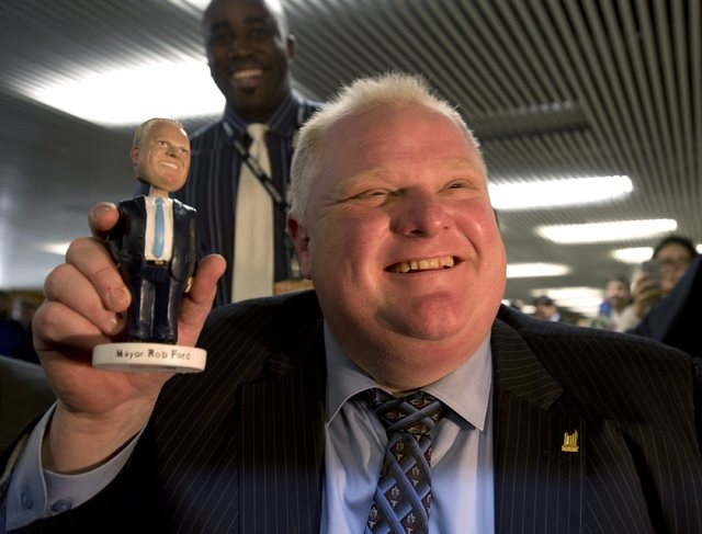 "Toronto Mayor Rob Ford holds a ""Robbie Bobbie"" bobblehead doll at Toronto city hall on Tuesday. Up to 300 people lined up at City Hall Tuesday to buy the dolls for $20 each, with the proceeds goin ..."