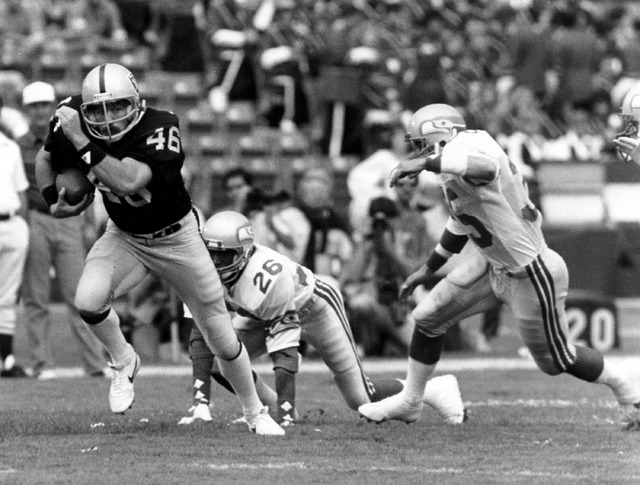 In this Oct. 30, 1983 photo provided by the NFL, Los Angeles Raiders tight end Todd Christensen (46) runs with the football after making a catch during a football game against the Seattle Seahawks ...