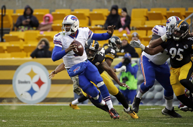 In this Nov. 10, 2013, file photo, Buffalo Bills quarterback EJ Manuel, left, is flushed out of the pocket by Pittsburgh Steelers free safety Ryan Clark (25) and Jarvis Jones (95) during an NFL fo ...