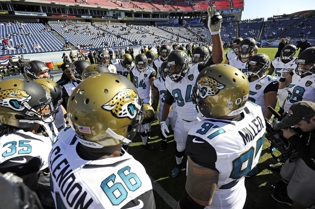 In this Nov. 10, 2013 file photo, Jacksonville Jaguars defensive end Jeremy Mincey (94) fires up his teammates before an NFL football game against the Tennessee Titans in Nashville, Tenn. As TV ra ...