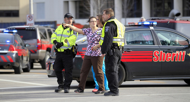 Medical personnel speak with law enforcement at the scene of a shooting at Children's Hospital of Wisconsin on Thursday, Nov. 14, 2013 in Wauwatosa, Wis.  Police officers shot and wounded a man in ...