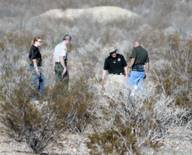 Forensic anthropologists and San Bernardino County Sheriff Department officials investigate shallow graves where human remains were found in a remote area near Quarry and Stoddard Wells roads in V ...