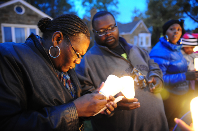 In this Nov. 6, 2013 file photo Charles Hannah lights Theresa Walker's candle, left,  at a vigil for Renisha McBride in the front of the home where she was shot in Dearborn Heights, Mich. Prosecut ...