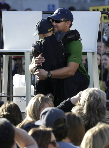 Miles Scott, dressed as Batkid, hugs his father Nick at a rally outside of City Hall in San Francisco, Friday, Nov. 15, 2013. (AP Photo/Jeff Chiu)