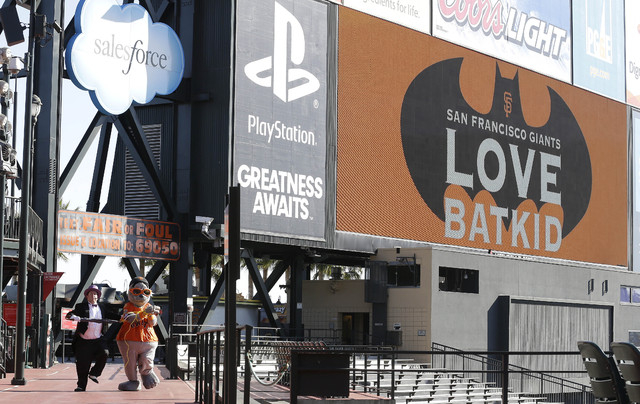 The scoreboard at AT&T Park displays a sign for Miles Scott, as Batkid, as the Penguin, bottom left, kidnaps San Francisco Giants mascot Lou Seal in San Francisco, Friday, Nov. 15, 2013. (AP Photo ...
