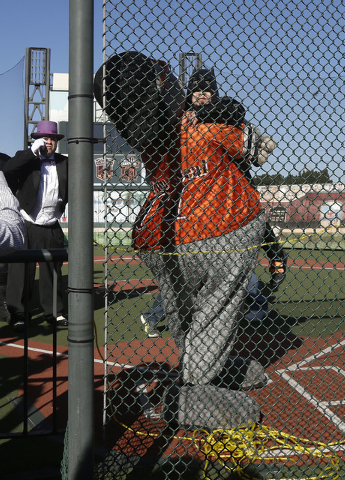 Miles Scott, as Batkid, right facing, gets hugged by San Francisco Giants mascot after Batkid and Batman rescued him from the Penguin, left, at AT&T Park in San Francisco, Friday, Nov. 15, 2013. ( ...