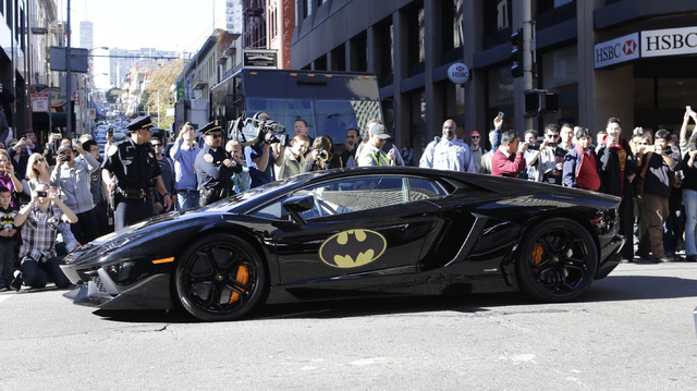 The crowd cheers as Miles Scott, 5, dressed as Batkid, as he rides inside the Batmobile in San Francisco on Friday, Nov. 15, 2013. (AP Photo/Bay Area News Group, Gary Reyes)
