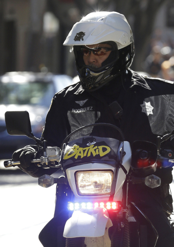 A San Francisco Police Officer with a Batkid sign on his bike waits for the arrival of Miles Scott, dressed as Batkid, in San Francisco, Friday, Nov. 15, 2013. (AP Photo/Jeff Chiu)