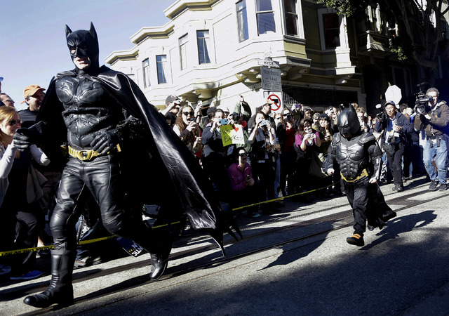 Miles Scott, dressed as Batkid, right, runs with Batman after saving a damsel in distress in San Francisco, Friday, Nov. 15, 2013. (AP Photo/Jeff Chiu)