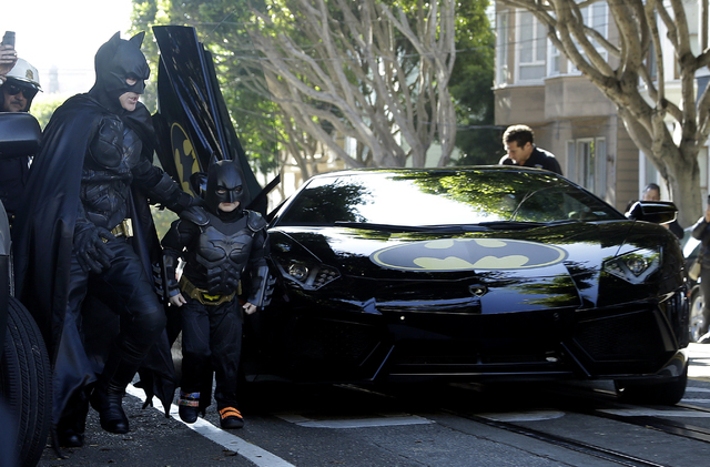 Miles Scott, dressed as Batkid, second from left, exits the Batmobile with Batman to save a damsel in distress in San Francisco, Friday, Nov. 15, 2013. (AP Photo/Jeff Chiu)