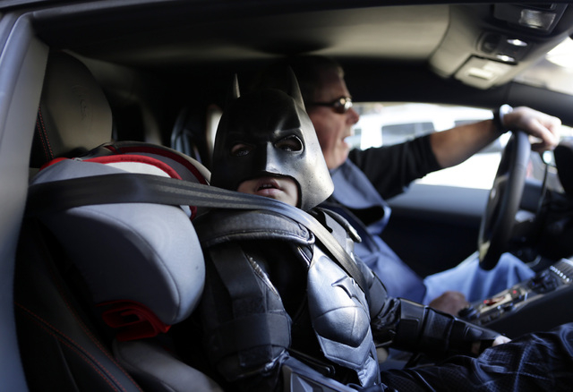"Miles Scott, 5, dressed as Batkid, waits in a Lamborghini ""Batmobile"" as he and Batman get ready to stop a bank robbery in San Francisco, Friday, Nov. 15, 2013. (AP Photo/Bay Area News Group, Gary ..."