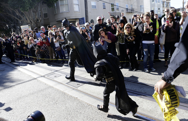 Miles Scott, 5, dressed as Batkid, follows Batman as they go to rescue a damsel in distress in San Francisco, Friday, Nov. 15, 2013. (AP Photo/Bay Area News Group, Gary Reyes)