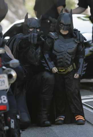 Batman assists Miles Scott, 5, dressed as Batkid, as he prepares to save a damsel in distress in San Francisco on Friday, Nov. 15, 2013. (AP Photo/Bay Area News Group, Gary Reyes)