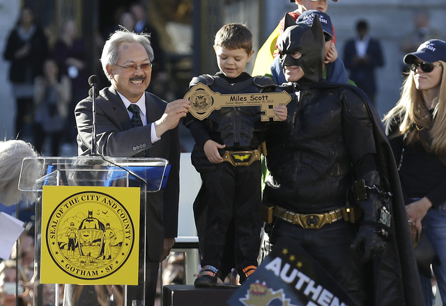 Miles Scott, dressed as Batkid, stands next to Batman as he receives the key to the city from San Francisco Mayor Ed Lee, left, at a rally outside of City Hall in San Francisco, Friday, Nov. 15, 2 ...