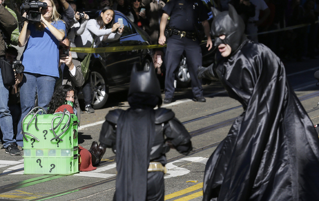 Miles Scott, dressed as Batkid, center, walks with Batman to save a damsel in distress on the Cable Car line in San Francisco, Friday, Nov. 15, 2013. (AP Photo/Jeff Chiu)