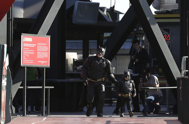 Miles Scott, dressed as Batkid, right, walks with Batman as they look for the Penguin at AT&T Park in San Francisco, Friday, Nov. 15, 2013. (AP Photo/Jeff Chiu)