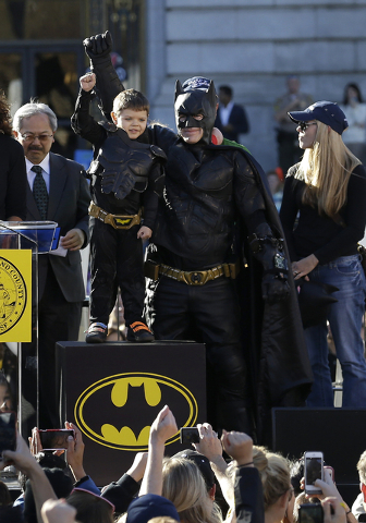 Miles Scott, dressed as Batkid, second from left, raises his arm next to Batman at a rally outside of City Hall with Mayor Ed Lee, left, and his mother Natalie Scott in San Francisco, Friday, Nov. ...