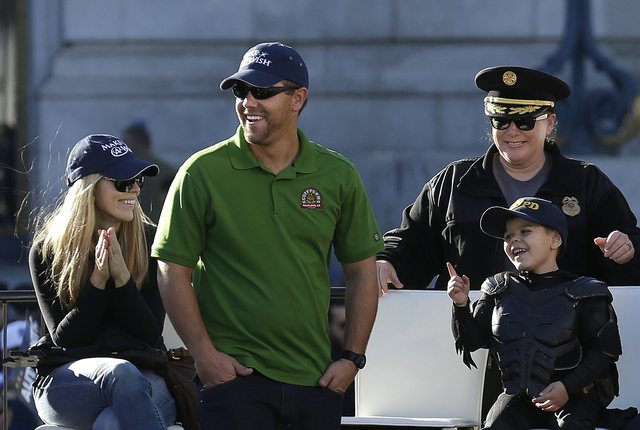 Miles Scott, dressed as Batkid, bottom right, smiles at a rally outside of City Hall with his parents, Natalie and Nick, and San Francisco Police Chief Joanne Hayes-White in San Francisco, Friday, ...