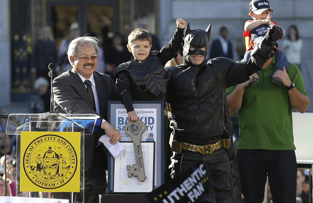 Miles Scott, dressed as Batkid, second from left, raises his arm next to Batman at a rally outside of City Hall with Mayor Ed Lee, left, and his father Nick and brother Clayton, at right, in San F ...