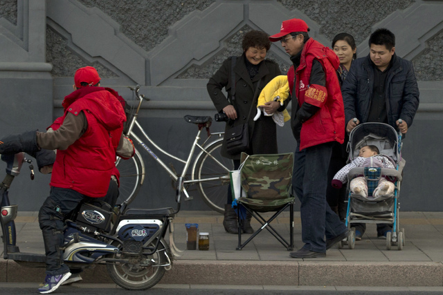 A child rest in a stroller on the streets of Beijing, China, on Tuesday. China announced a loosening of family planning rules that limit many couples to a single child in the first substantial cha ...
