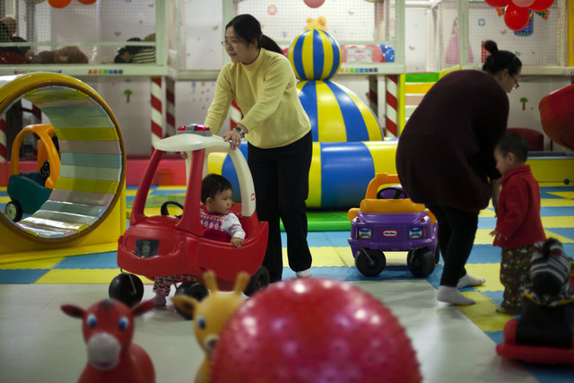 Parents play with their children at a kid's play area in a shopping mall in Beijing in January. China will loosen its decades-old one-child policy and abolish a much-criticized labor camp system,  ...