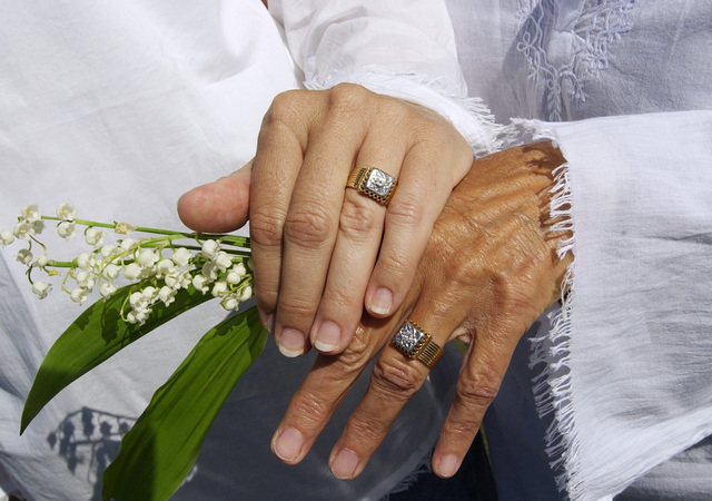 In this May 20, 2004 file photo, Suzanne Nightingale, 49, left, and Kathleen Clementson, 62, of Cape Coral, Fla., display their rings at their wedding ceremony on Saint's Landing Beach in Brewster ...