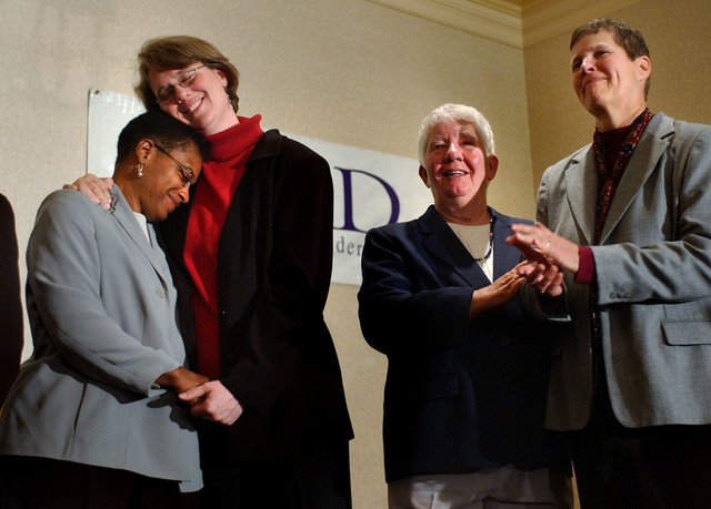 In this Nov. 18, 2003 file photo Heidi Norton, second from left, hugs her partner Gina Smith, both of Northampton, Mass., during a news conference in Boston regarding the Massachusetts Supreme Jud ...