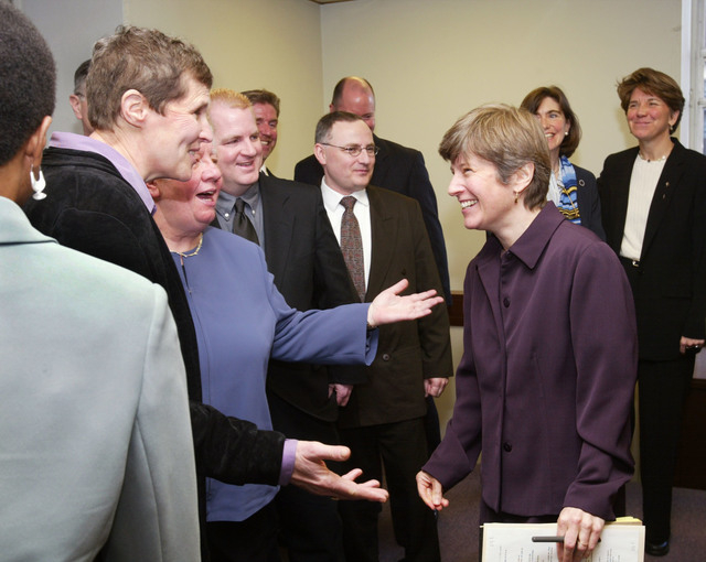 In this March 4, 2003 file photo, attorney Mary Bonauto, right, smiles while surrounded by gay couples after a news conference in Boston following oral arguments at the Supreme Judicial Court on t ...