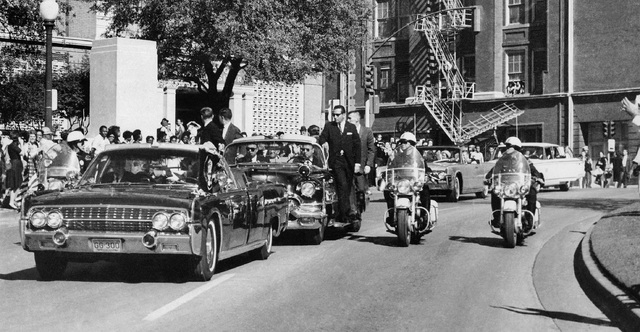 FILE - In this Friday, Nov. 22, 1963 file photo, seen through the foreground convertible's windshield, President John F. Kennedy's hand reaches toward his head within seconds of being fatally shot ...
