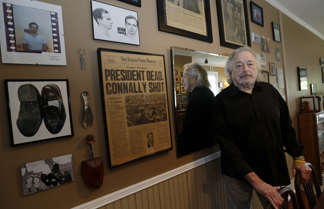 In this Tuesday, Nov. 5, 2013 photo, John Brewer stands next to memorabilia at his home in Austin, Texas. Brewer helped direct police to Lee Harvey Oswald in Dallas' Texas Theatre after President  ...