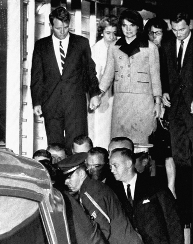 FILE - In this Friday, Nov. 22, 1963 file photo, Jacqueline Kennedy, with bloodstains on her clothes, holds hands with her brother-in-law, Attorney General Robert Kennedy, as the coffin carrying t ...
