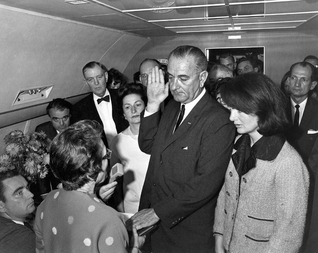 FILE - In this Friday, Nov. 22, 1963 photo from the White House via the John Fitzgerald Kennedy Library in Boston, Lyndon B. Johnson is sworn in as president as Jacqueline Kennedy stands at his si ...