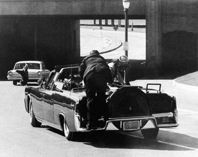 FILE - In this Friday, Nov. 22, 1963 file photo, President John F. Kennedy slumps down in the back seat of the Presidential limousine as it speeds along Elm Street toward the Stemmons Freeway over ...