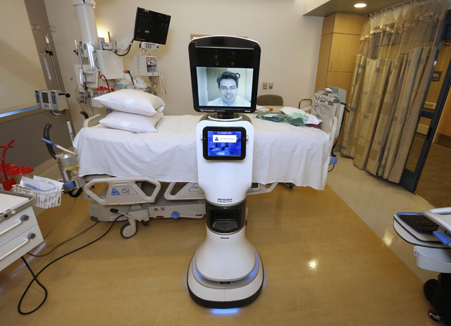 In this photo taken Wednesday, Nov. 6, 2013 Dr. Alan Shatzel, medical director of the Mercy Telehealth Network, is displayed on the monitor RP-VITA robot at Mercy San Juan Hospital in Carmichael,  ...