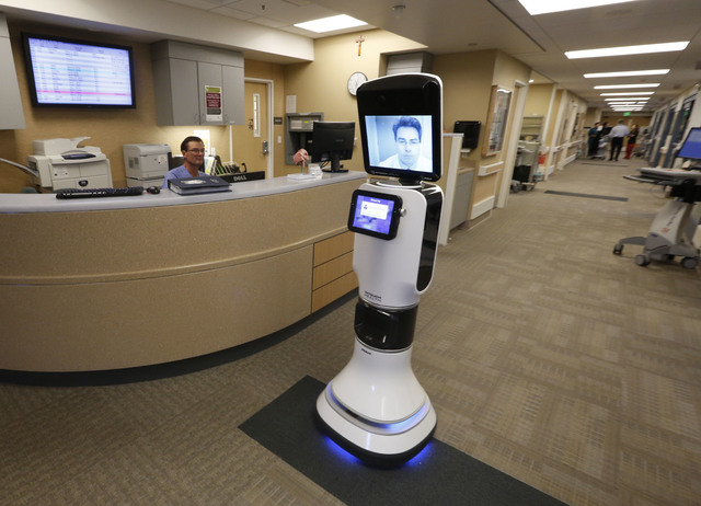 In this photo taken Wednesday, Nov. 6, 2013 Dr. Alan Shatzel, medical director of the Mercy Telehealth Network, is displayed on the monitor RP-VITA robot as it moves through Mercy San Juan Hospita ...