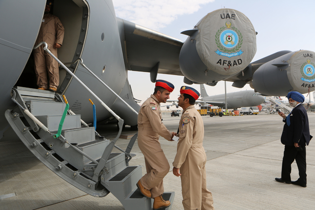 UAE pilots greet each other at the steps of a Boeing C-17 Globemaster III, a large military transport aircraft of the UAE Air forces during the opening day of the Dubai Airshow in Dubai, United Ar ...