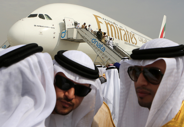 Emirati officials greet each other in front of an Emirates Airbus A380 on display during the opening day of the Dubai Airshow in Dubai, United Arab Emirates, Sunday Nov. 17, 2013. The Dubai Airsho ...
