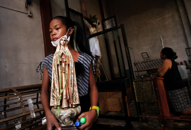 A girl holds a statue of the Virgin Mary prior to a Mass at St. Nino church that was partially damaged by Typhoon Haiyan in Tacloban, Philippines, Sunday, Nov. 17, 2013.  Typhoon Haiyan, one of th ...