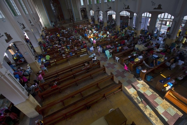Typhoon Haiyan survivors enter a Catholic cathedral, where crowds of homeless people are squatting in Tacloban, Philippines, before church mass on Sunday Nov. 17, 2013. (AP Photo/David Guttenfelder)